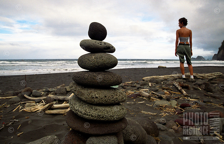 Young woman standing near rock alter, Pololu black sand beach, North Kohala, Big Island