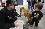 Sean McHaney, with the VFW Post 3819 of Reno, and his dog Rex play with Kamden McCormick, 15 months, while waiting for members of the 422nd Expeditionary Signal Battalion of the Nevada National Guard who returned home Sunday, Jan. 15, 2012, after a yearlong deployment to Afghanistan. Hundreds of family and friends greeted the soldiers at the Nevada Air Guard Base in Reno, Nev..Photo by Cathleen Allison