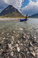 Paddler carries her pack raft across a shallow section of the Marsh Fork of the Canning River in the Arctic National Wildlife Refuge, Brooks Range mountains, Alaska.