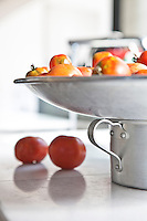 A simple metal pot in the kitchen is filled with home-grown tomatoes