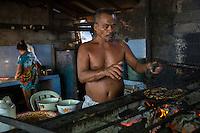 Bali, Indonesia.  Cook Grilling Fish over Charcoal Fire, Jimbaran Fish Market.