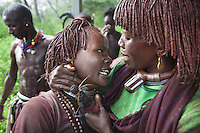 Ethiopia. Southern Nations, Nationalities, and Peoples' Region. Omo Valley. Turmi. Hamar tribe (also spelled Hamer). Pastoralist group. Two women are sharing their intense emotions. Hamar women wear an elaborately decorated goatskin, often colored with beads and cowries. Beaded necklaces, bracelets and waistbands adorn their bodies. They also wear thick copper necklaces announcing their marital status; a lather long tipped necklace and two copper necklaces if they are the first wife and only two copper necklaces if they are second, third, fourth wife to one man. Hamer women indulge in elaborate hairdressing by decorating their hair with clay and butter twisted into a striking long plait. The Omo Valley, situated in Africa's Great Rift Valley, is home to an estimated 200,000 indigenous peoples who have lived there for millennia. Amongst them are 60'000 to 70'000 Hamar, an Omotic community inhabiting southwestern Ethiopia. They live in Hamer woreda (or district), a fertile part of the Omo River valley, in the Debub Omo Zone of the Southern Nations, Nationalities, and Peoples Region (often abbreviated as SNNPR) which is one of the nine ethnic divisions of Ethiopia. 9.11.15 © 2015 Didier Ruef