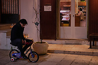 Italy. Apulia Region. Cisternino. Night time. A young man rides a child's bicycle and thinks alone in the darkness. An outside sign prohibits people to sit on the stairs. A man reads a newspaper inside in a restaurant specialized on raw meat cooked on fire. An elderly woman is seated at the restaurant counter's cashier. Cisternino is town and a comune. In 2014, Cisternino was declared the cittaslow city of the year. Cittaslow is an organisation founded in Italy and inspired by the slow food movement. Cittaslow's goals include improving the quality of life in towns by slowing down its overall pace, especially in a city's use of spaces and the flow of life and traffic through them. Cittaslow is part of a cultural trend known as the slow movement. Apulia (Puglia) is a region in Southern Italy.6.12.18  © 2018 Didier Ruef