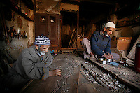 Father and son in woodcarving work shop. Father draws a pattern on a board while the son have lunch. Srinagar, Kashmir, India. © Fredrik Naumann/Felix Features