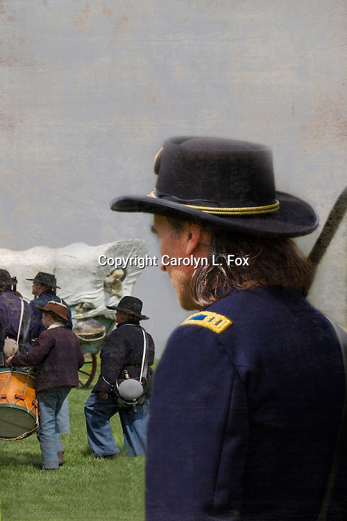 A union officer wtches as his man march by a covered wagon during a Civil War reenactment.