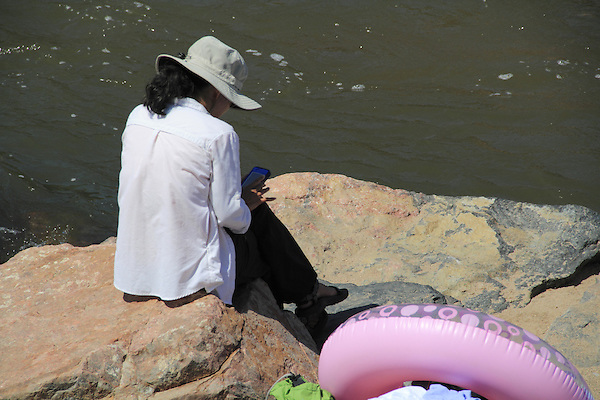 Asian woman text messaging while sitting along river in Boulder, Colorado. .  John offers private photo tours in Denver, Boulder and throughout Colorado. Year-round Colorado photo tours.
