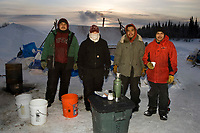 Nikolai volunteers pose for picture during break in the action 2006 Iditarod near sunset Alaska Winter
