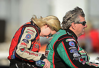 Sept. 29, 2012; Madison, IL, USA: NHRA funny car driver Courtney Force (left) leans against father John Force as they ride a scooter during qualifying for the Midwest Nationals at Gateway Motorsports Park. Mandatory Credit: Mark J. Rebilas-
