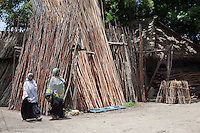 Zanzibar, Tanzania.  Mangrove Poles for Sale.  Used for scaffolding or other construction.  Historically these were transported back to the Persian Gulf in dhows where they were used as ceiling supports in the traditional houses common until the early 20th. century.  Zanzibari Women Wearing Kitenge Cloth.