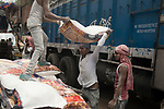 A daily wage laborer helps another to lift a heavy sack on his head while another labor waits for his turn at burrabazzar in Kolkata.  Whole sale market reopened in Kolkata few days back midst 21 days lock down in India due to covid 19 pandemic. Kolkata, West Bengal, India. Arindam Mukherjee.