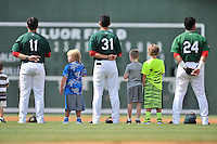Red Sox prospects Michael Chavis (11), Javier Guerra (31) and Yoan Moncada (24) of the Greenville Drive stand for the National Anthem before a game against the Charleston RiverDogs on Sunday, August 16, 2015, at Fluor Field at the West End in Greenville, South Carolina. Charleston won, 6-2. (Tom Priddy/Four Seam Images)