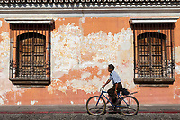 Antigua, Guatemala.  Man on Bicycle Rides Past an Old House with Flaking Paint.