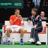 10-02-12, Netherlands,Tennis, Den Bosch, Daviscup Netherlands-Finland, , Thiemo de Bakker eet een banaan op de bank met captain Jan Siemerink.