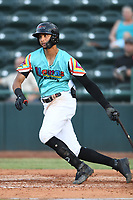 Pedro Gonzalez (4) of Las Llamas de Hickory follows through on his swing during a game against Los Rapidos de Kannapolis at L.P. Frans Stadium on July 17, 2019 in Hickory, North Carolina. The Llamas defeated the Rapidos 7-5. (Tracy Proffitt/Four Seam Images)