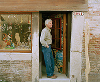 A traditional toy artisan stands in the doorway of his Venetian shop.