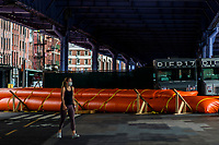 """NEW YORK, NY - AUGUST 4: woman walks next to water barriers used to prevent flooding at the South Street Seaport as city gets ready for tropical storm Isaias on August 4, 2020 in New York City. The Tri-State area """"New York, New Jersey and Connecticut"""" is preparing for torrential rain, strong winds from Tropical storm Isaias. (Photo by Eduardo MunozAlvarez/VIEWpress)"""