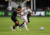 Cristian Pavón #10 of LA Galaxy tries to dribble by Eddie Segura #4 of LAFC