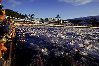 Photographers and spectators cheer the multitudes of swimmers at the start of the grueling 2.4 mile swim during the annual Ironman triathlon, Kailua-Kona, Hawaii.