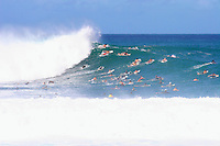 A wave spits as the crowd paddles over it at Pipeline on Oahu's North Shore.