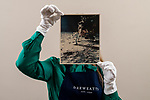 Pictured: Sales Coordinator Lulu Randall  holds up  an original print of Buzz Aldrin as he erects the solar wind experiment on the surface of the moon with an estimated value of £1,500-£2,500 ahead of auction today [WEDNESDAY] at Dreweatts Auction House in Newbury, Berks.<br /> <br /> Neil Armstrong took the first photograph of Buzz Aldrin with his feet on the lunar surface on the 20th July 1969. The two black spots in the sky above the horizon and the foggy areas seen in the photograph were caused by the refraction of sunlight in the lens of Armstrong's camera. <br /> <br /> Some of the most historic photographs chronicling the history of man's exploration of space, from early expeditions, to some of the latter trips of the 1990s will be sold at auction.  Over 600 images, many of which capture historic moments, such as the first humans in space, the first spacewalk and the first moon landing will be auctioned today on March 17th 2021 as part of the Space Exploration Photography and Ephemera auction by Dreweatts.<br /> <br /> © Jordan Pettitt/Solent News & Photo Agency<br /> UK +44 (0) 2380 458800