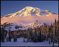 A December's setting sun momentarily turns a cloud pink, as it brushes along the base of a snowy Mount Rainier, an active volcano at 14,410 feet in height. Photographed in the Paradise area, Mount Rainier National Park, Washington State.....A photographic print of this image is displayed in Mount Rainier National Park's Permanent Collection. Photographed in 6X7 format on Velvia 50 film.