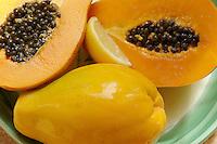 Plate of ripe papaya fruit with lemon wedge