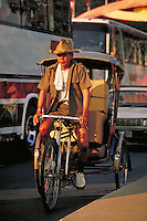 Three wheeled bicycle taxi in motion with packages. tour buses in background. Chiang Mai, Thailand.