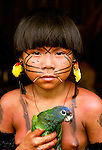 With tiny birds as earrings, a Yanomamo girl holds her pet parrot. The Yanomamo live in the Amazon rainforest on the border of Venezuela and Brazil.