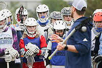 Students listen as professional lacrosse player, Tom Schreiber, gives instructions on technique, Friday, April 16, 2021 during a lacrosse clinic at Phillip's Park in Bentonville. Lacrosse is a rapidly growing sport in Northwest Arkansas. The Ozark Mountain Lacrosse program held a clinic for players in grades 7-12. Check out nwaonline.com/210417Daily/ for today's photo gallery. <br /> (NWA Democrat-Gazette/Charlie Kaijo)
