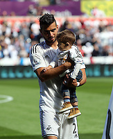 Pictured: Jordi Amat with his baby son. Saturday 23 August 2014<br /> Re: Premier League, Swansea City FC v Burnley at the Liberty Stadium, south Wales