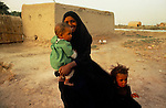 Marsh Arabs. Southern Iraq.  Marsh Arab woman with children and adobe home on banks of river Tigris. 1984