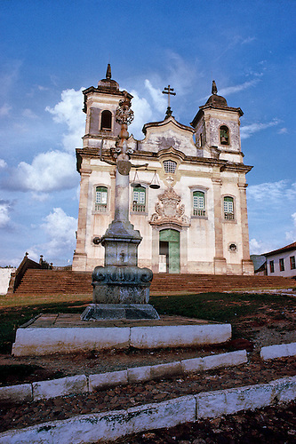 Mariana, Brazil. The front of the Church of Sao Francisco de Assis with pillar monument with iron arms with scales and sword.