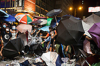 Pro-democracy protesters are seen behind their umbrellas, shortly before the Hong Kong police lost control of the area, and thus ceding it back to the protesters, who had only just lost it to the police hours earlier in a pre-dawn raid, Mong Kok, Kowloon, Hong Kong, China, 18 October 2014.