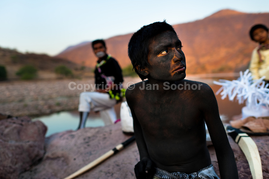 """A Cora Indian boy, with body and face painted all over, prepares himself for the religious ritual celebration of Semana Santa (Holy Week) in Jesús María, Nayarit, Mexico, 21 April 2011. The annual week-long Easter festivity (called """"La Judea""""), performed in the rugged mountain country of Sierra del Nayar, merges indigenous tradition (agricultural cycle and the regeneration of life worshipping) and animistic beliefs with the Christian dogma. Each year in the spring, the Cora villages are taken over by hundreds of wildly running men. Painted all over their semi-naked bodies, fighting ritual battles with wooden swords and dancing crazily, they perform demons (the evil) that metaphorically chase Jesus Christ, kill him, but finally fail due to his resurrection. La Judea, the Holy Week sacred spectacle, represents the most truthful expression of the Coras' culture, religiosity and identity."""