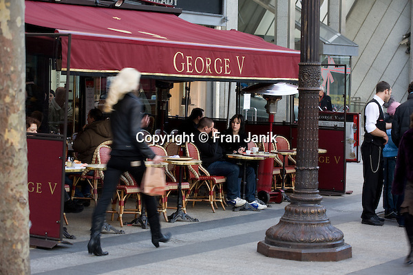A woman walks briskly by the George V cafe on the Champs Elysees in Paris France, as patrons sip coffee.