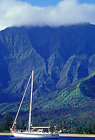 Couple abord sailboat in Hanalei Bay, with Na Molokama mountain, off Hanalei Beach, North Shore, Kauai, Hawaii