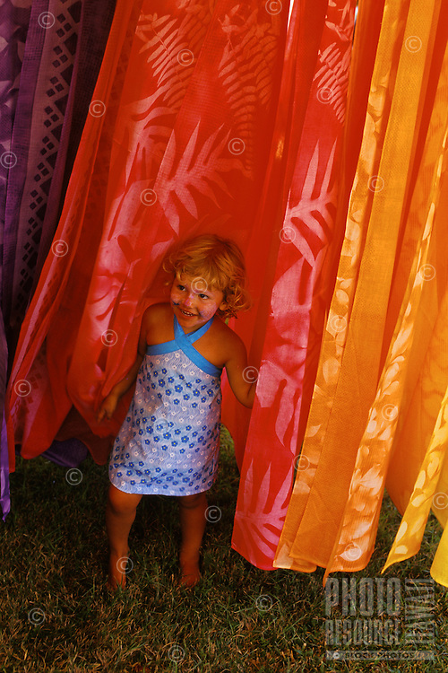 Young girl playing among hand dyed pareos at Haleiwa Art Festival, Haliewa Beach Park, North Shore, Oahu