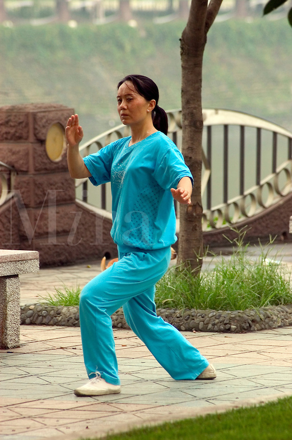 Chinese woman practices  Tai Chi in a city park along the Jin River - Chengdu, China in Sichuan Province