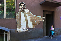 Armenia. Yerevan.  A lonely young girls stands on the sidewalk close to an elderly building's entrance. The building was built during the former soviet time. On the wall, a pixelized and vanishing face of a young fashionable man. Yerevan, sometimes spelled Erevan, is the capital and largest city of Armenia. 2.10.2019 © 2019 Didier Ruef