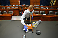 The area around the name tag for the Director of the National Institute for Allergy and Infectious Diseases Dr. Anthony Fauci is sanitized before he arrives to testify before the House Committee on Energy and Commerce on the Trump Administration's Response to the COVID-19 Pandemic, on Capitol Hill in Washington, DC on Tuesday, June 23, 2020.  <br /> Credit: Kevin Dietsch / Pool via CNP/AdMedia