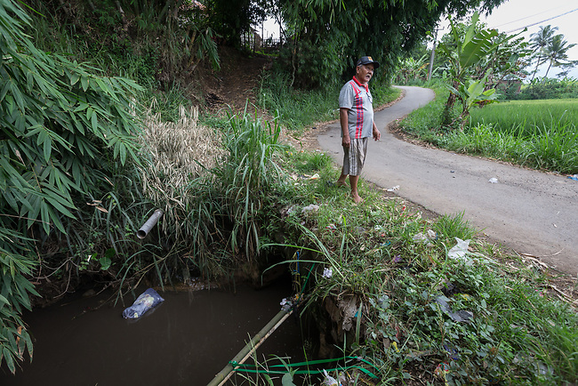 29 JAN, 2018, Bandung, Indonesia: Rahmat Sutrisno stands at the base of the driveway to his home where a toxic canal used by five industrial companies to dump untreated waste - including dyes-  feeds into the Citarum river, listed as one of the most polluted rivers in the world.  It will soon be the main water supply system for Jakarta as the bores that have been dug into the aquifers dry but it also supports agriculture, fishery, industry, sewerage and electricity.  The Indonesian Government is moving to urgently try to clean the system up but it is fighting massive infrastructure issues and toxic industrial dumping.    Picture by Graham Crouch/The Australian