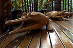 Milne Bay, Papua New Guinea; crocodile wood carvings at the entrance to the main building at Tawali Resort , Copyright © Matthew Meier, matthewmeierphoto.com