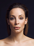 Beauty portrait of a woman with brown hair and clean natural makeup in her early thirties isolated on black background Image © MaximImages, License at https://www.maximimages.com