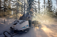 Hunter, Ion Maxsimovic revs up the engine of his snowmobile in order to warm it up on a typically cold morning. Temperatures in the region can get as low as minus 50 degrees celsius.