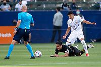 CARSON, CA - MAY 8: Adam Saldana  #43 of the Los Angeles Galaxy straddles Eduard Atuesta #20 of LAFC during a game between Los Angeles FC and Los Angeles Galaxy at Dignity Health Sports Park on May 8, 2021 in Carson, California.
