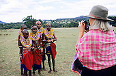 Lolgorian, Kenya. White female tourist taking a photograph of Maasai girls.
