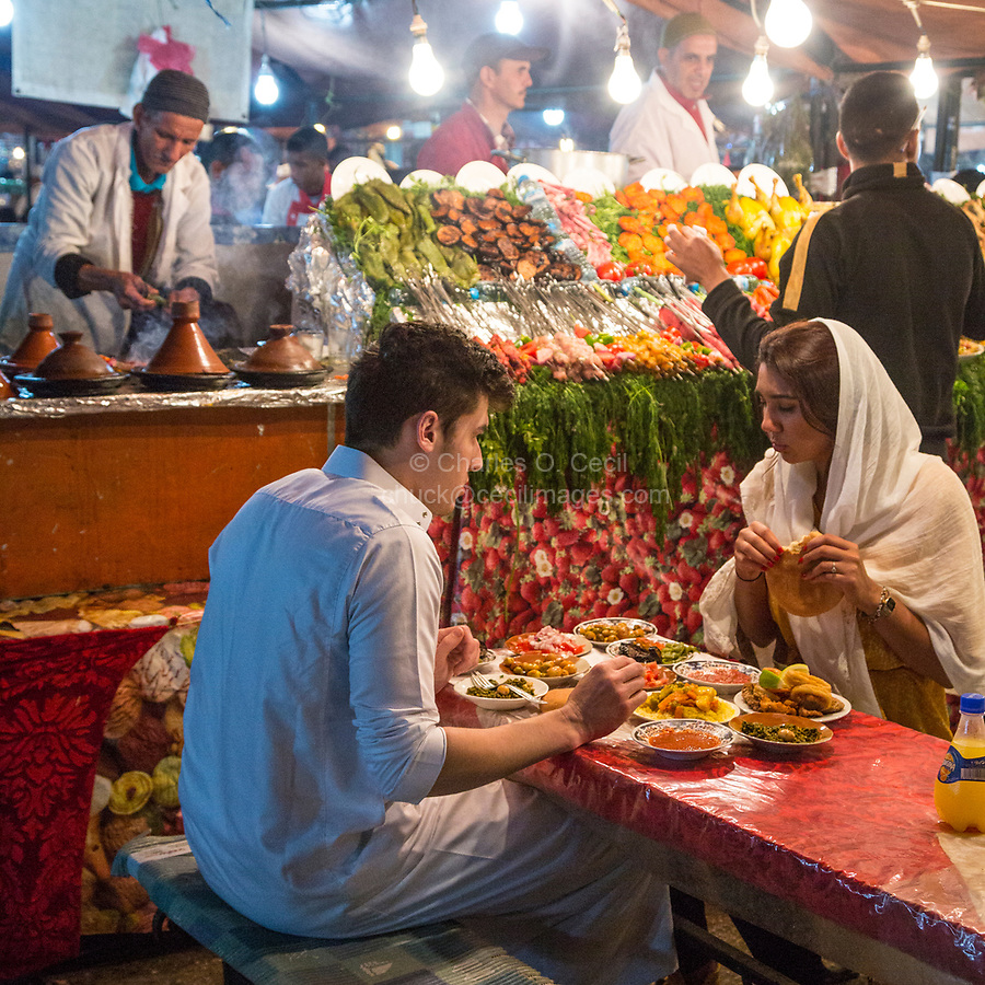Marrakesh, Morocco.  Young Couple Eating Dinner at Food Stall, Place Jemaa El-Fna.