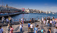 Travel Photograph.<br /> The busy Istanbul seaport on the Bosphorus Strait. Crowds of people on the famous double deck Galata bridge are busy fishing and dining while overlooking this busy waterway.<br /> The streets are filled with people as they walk along the seaport. In the distance are the buildings and ships along the Bosphorus Strait.