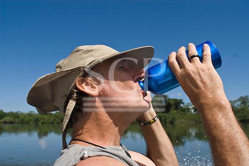 Pará State, Brazil. Xingu River. Patrick Cunningham drinking water from an aluminium bottle.