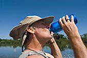 Pará State, Brazil. Xingu River. Patrick Cunningham drinking water from an aluminium bottle.